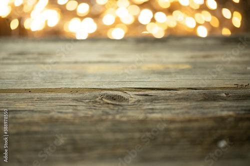 Fototapeta Pusty stół drewniany z rozmytym tłem ze światełkami i lampkami o ciepłej barwie na święta obraz