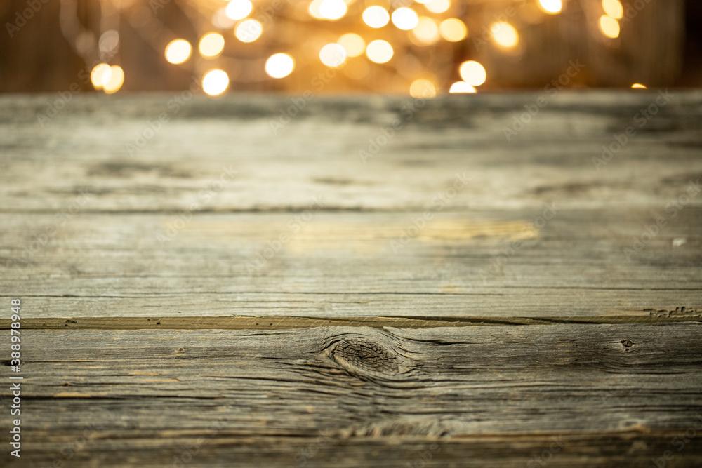 Fototapeta Pusty stół drewniany z rozmytym tłem ze światełkami i lampkami o ciepłej barwie na święta - obraz na płótnie