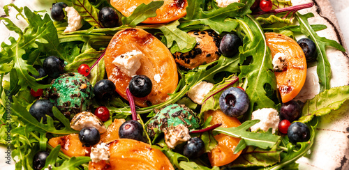 Fototapeta Easy recipe for summer salad with goat cheese, grilled apricots, arugula, berries, close-up obraz