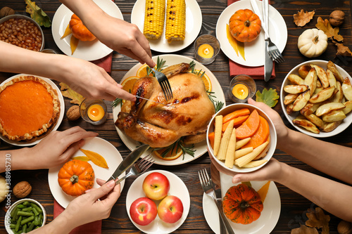 Fototapeta People eating cooked turkey at wooden table, top view. Thanksgiving day celebration obraz