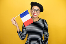 Young Beautiful Brunette Woman Wearing French Beret And Glasses Over Yellow Background Holding Flag Of French With A Happy Face Standing And Smiling With A Confident Smile Showing Teeth
