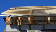 Unfinished Roofing Construction With A Close-up On Ceiling Joists, Wooden Rafters, Strutting Beams, And Roof Sheathing On A Vapor Barrier Of A Gable Roof.