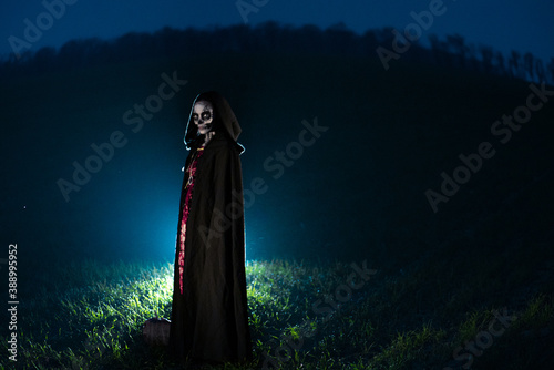 Foto Woman stands in Halloween costume of death against dark sky.