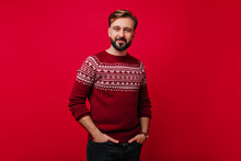 Confident White Man With Beard Posing With Hands In Pockets. Studio Shot Of Handsome Guy With Dark Hair Wears Norwegian Sweater.