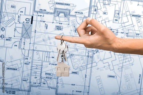 Drawing architecture or construction blueprint and hand with key