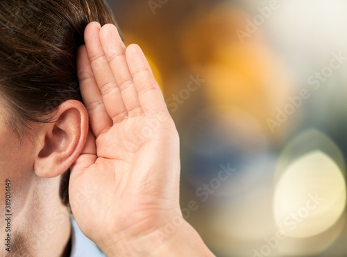 Human holds his hand near his ear and listening