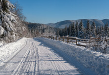 Secondary Countryside Alpine Road To Remote Mountain Hamlet Through Snowy Fir Forest, Snow Drifts And Wood Fence On Wayside