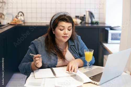 Fotografija Cute curvy young Caucasian woman in denim jacket writing down in copybook while learning online using laptop, sitting at kitchen table with fresh orange juice