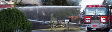 A Residential Home Burns In A House Fire As Firefighters Spay Water From A Hose In An Effort To Put It Out.