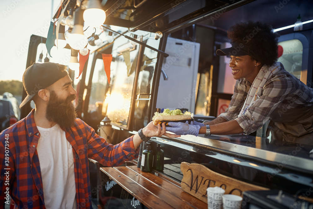 Fototapeta afro-american female employee gives with care sandwich to young hipster male customer