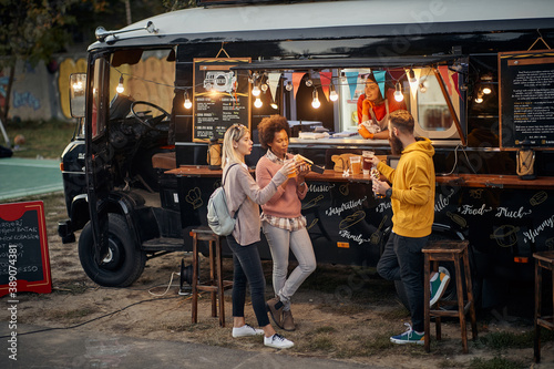 Obraz group of people socializing while eating outdoor in front of modified truck for fast food - fototapety do salonu