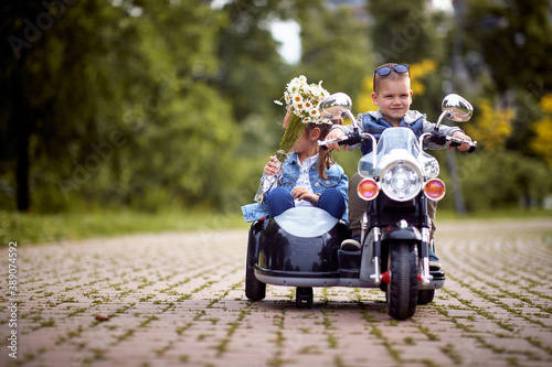 Foto Happy little boy and a girl driving in a toy motocycle