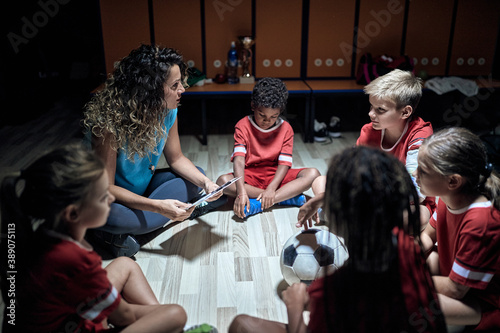 A female coach and her little players discussing strategy for the match. Children team sport