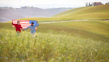 A Happy Couple Walking A Meadow With Unfurled American Flag Above Heads. Election, Campaign, Freedom Concept