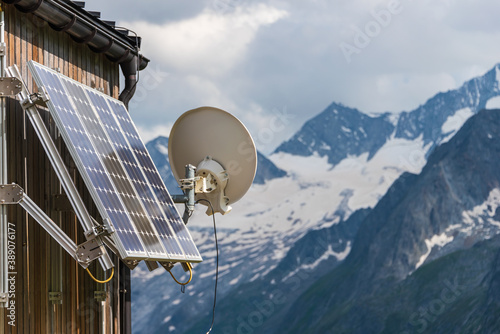 Cuadros en Lienzo PV solar panels and satellite dish antenna at the wall of a wooden building with snowy mountains in the background