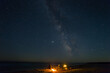 man sit on a chair near a fire on a sea coast under starry sky with milky way, night travel camping scene