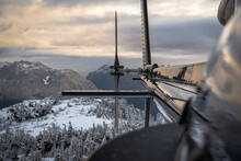 Looking Down The Side Of A Black Helicopter Towards The Tail Rotor Over Snowy Mountains