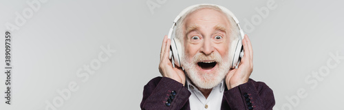 Excited senior man listening music in wireless headphones isolated on grey, banner