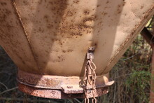 Old Rusty Metal Farm Animal Food Grain Feeder. Close Up Of The Bottom.