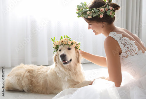 Fotografiet Bride and adorable Golden Retriever wearing wreath made of beautiful flowers ind