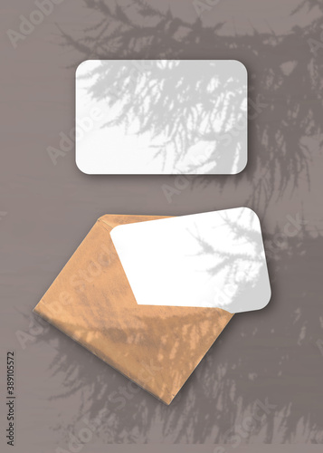 Papel de parede An envelope with two sheets of textured white paper on the brawn background of the table