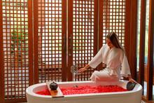 Pretty Slim Woman Wearing Bathrobe Sitting On Edge Of Bathtub Filling Up With Water. Bath Full Of Flower Petals