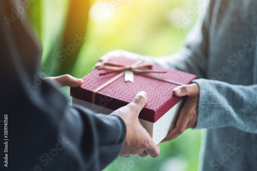 Closeup image of a man giving a woman a gift box Canvas