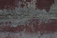 Photo Of An Old Texture Wall. The Paint Was Crumbling. Cracks, Fractures, And Dents. In Shades Of Grey And Red Bordeaux.