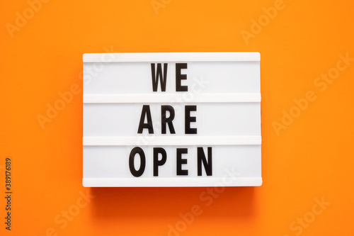Concept of the end of quarantine. Lightbox with text message We are open on a orange background. Hotel, store, cafe, business. Notification of the end of quarantine.