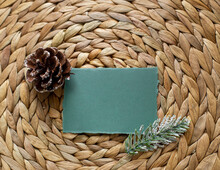 Green Blank Paper With Pine  Branch And Pine Cone On Yellow Tatched Mat. Modern Template Christmas Mock Up.  Flat Lay. Top View
