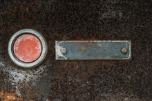Old Red Button With A Sign On A Metal Rust Background. Copy, Empty Space For Text