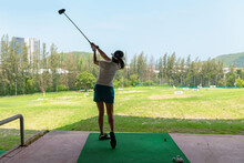 Asian Golfer Woman Swing Golf Ball Practice At Golf Driving Range On Evening On Time For Healthy Sport. Lifestyle And Sport Concept. Healthy Sport.