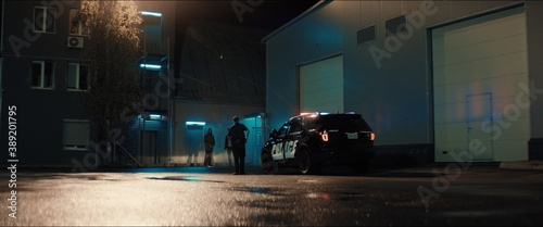 Fotografija WIDE Police officer exiting a car and approaching two multi-ethnic males suspects near industrial buildings at night
