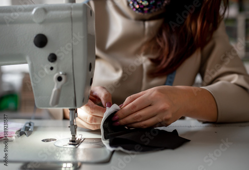 Fotografia, Obraz The girl sits in a mask and sews masks on a sewing machine to protect against covid-19