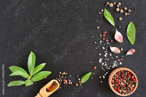 Fotografia Fresh bay leaf, allspice and pepper mix on dark stone background