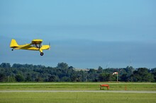 Small  Yellow Karatoo Crop Checker Propeller Airplane  Low Above The Runway Near A Windsock Coming In For Landing