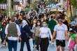 crowd goes up and down a busy shopping street wearing a protective mask