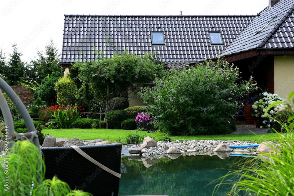 Fototapeta Pięknie zaprojektowany ogród wraz z naturalnym basenem z kamieni