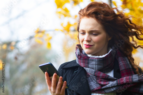 Fotografía Surprised woman typing a message, European female sending an SMS message to her mobile smartphone