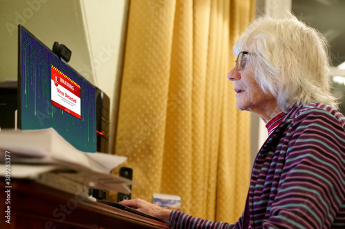 Valokuva Old elderly senior person with virus warning on computer monitor screen