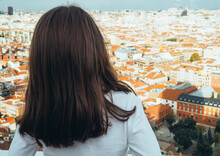 Back View Of A Little Girl Looking At The Skyline Of The City Of Madrid On A Sunny Afternoon From The Rooftop Of A Building