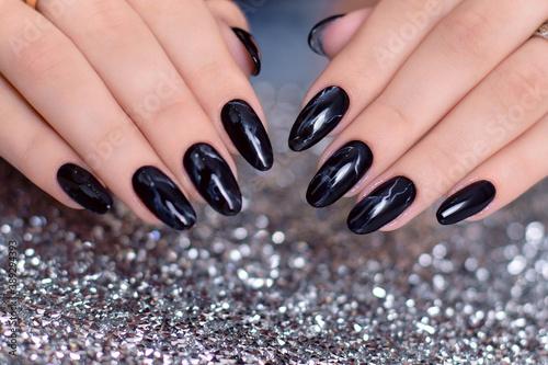 Beautiful female hands with fashion manicure nails, black gel polish, on glitter background