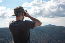 Man Looking Through Binoculars Wearing Hat And Tshirt At Mountain Hill Nature Forest Landscape. Travel Adventure Observer Future Concept