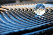 Beautiful Image With Lens Ball On A Metal Curved Bench Showing An Inverted Image In The Sphere. Space For Text.