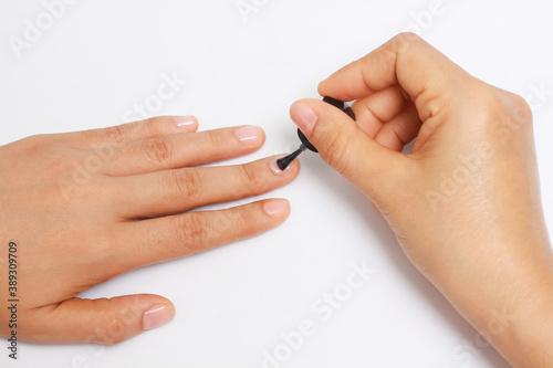 Fotografia, Obraz manicure applying, brushing fingernails with clear enamel, nail painting transpa