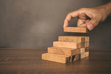 Close-up Hand Is Placing Wood Block Tower Stacked In Stair Step With Caution To Prevent Collapse Or Crash Concepts Of Financial Risk Management And Strategic Planning.