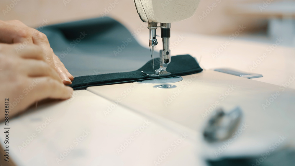 Fototapeta Woman seamstress works at a sewing machine