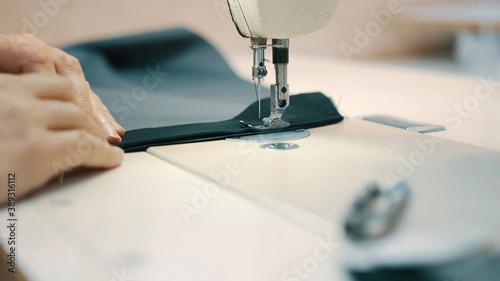 Fotografia, Obraz Woman seamstress works at a sewing machine