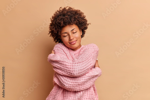 Pretty dark skinned curly woman embraces herself and closes eyes feels comfort in soft warm knitted sweater enjoys home tenderness tilts head poses against beige background Tableau sur Toile