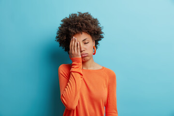 Fototapeta na wymiar Exhausted unhappy woman makes face palm and sighs from tiredness has sleepy expression fed up of working without rest wears orange jumper in one color with earrings. Upset depressed female model